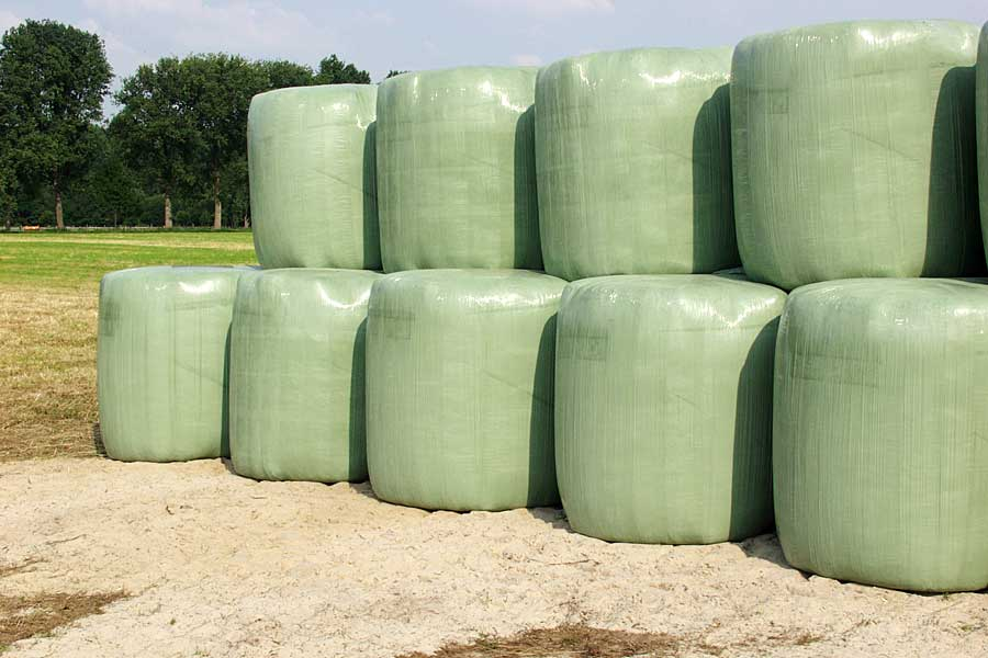 round bales stored on sandy ground, © balesilage.com